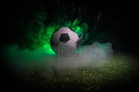 Photo for Traditional soccer ball on soccer field. Close up view of soccer ball (football) on green grass with dark toned foggy background. Selective focus - Royalty Free Image