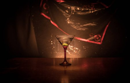Photo for Glass with martini with olive inside. Close up view of glass with club drink on dark foggy toned background. Selective focus. Club drink concept - Royalty Free Image