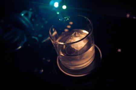 Photo pour Verre à whisky avec des glaçons à l'intérieur sur contrôleur dj dans la discothèque. DJ Console avec boisson club à la fête de la musique en boîte de nuit avec les lumières disco. Mise au point sélective - image libre de droit