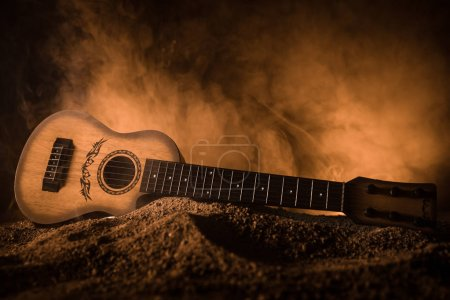 Photo for Music concept. Acoustic guitar isolated on a dark background under beam of light with smoke with copy space. Guitar Strings, close up. Selective focus. - Royalty Free Image
