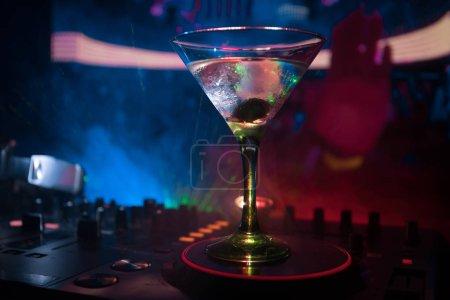 Photo pour Verre à martini avec olive à l'intérieur sur contrôleur dj en boite de nuit. DJ Console avec boisson club à la fête de la musique en boîte de nuit avec les lumières disco. - image libre de droit