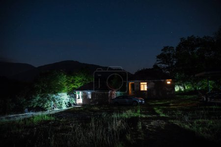 Photo for Mountain night landscape of building at forest at night with moon or vintage country house at night with clouds and stars. Summer night. Photo taken with long exposure - Royalty Free Image