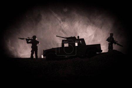 Photo pour Concept de la guerre. Silhouettes militaires scène sur fond de ciel de brouillard guerre de combat, la lutte contre les silhouettes ci-dessous nuageux Skyline At night. Scène de bataille. Véhicules jeep avec des soldats de l'armée. jeep de l'armée - image libre de droit