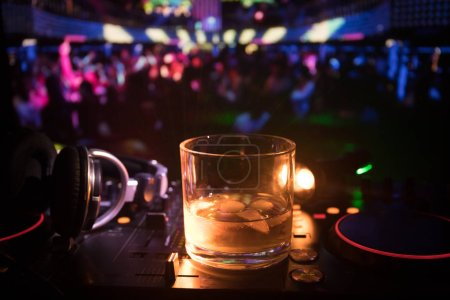 Photo for Glass with whisky with ice cube inside on dj controller at nightclub. Dj Console with club drink at music party in nightclub with disco lights. Selective focus - Royalty Free Image