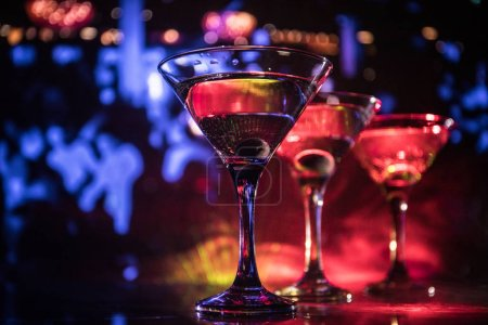 Photo for Several glasses of famous cocktail Martini, shot at a bar with dark toned foggy background and disco lights. Club drink concept. Selective focus - Royalty Free Image