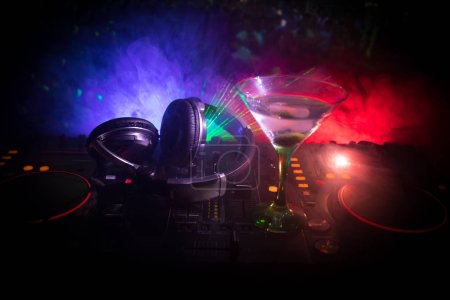 Photo for Glass with martini with olive inside on dj controller in night club. Dj Console with club drink at music party in nightclub with disco lights. - Royalty Free Image