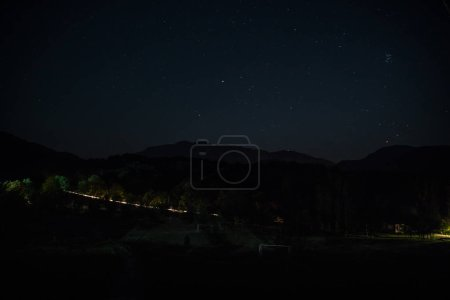 Photo for Beautiful night landscape with starry night mountains and forest. Night forest with green meadow and mountains in bright starry night or view of milky way - Royalty Free Image