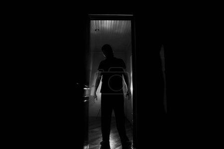 Photo for Silhouette of an unknown shadow figure on a door through a closed glass door. The silhouette of a human in front of a window at night. Scary scene halloween concept of blurred silhouette of maniac. - Royalty Free Image