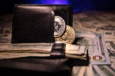 Photo pour Bitcoins dorés et argentés et beaucoup de dollars en portefeuille en cuir. Bitcoin avec dollar dans la bourse. Profiter de l'exploitation minière crypto-monnaies. Concentration sélective. Bussiness, commercial . - image libre de droit
