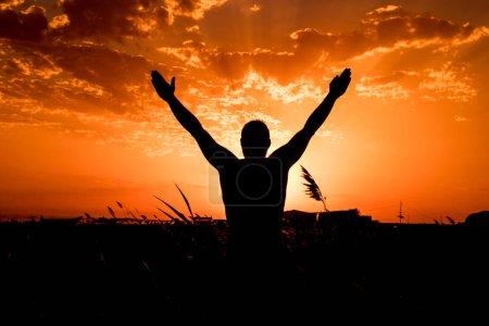 Photo pour Silhouette de l'homme avec leurs mains au coucher du soleil. - image libre de droit