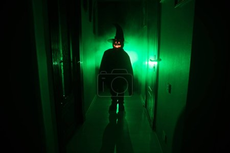 Photo for Halloween concept. Creepy silhouette in the dark corridor with pumpkin head. Toned light with fog on background. - Royalty Free Image