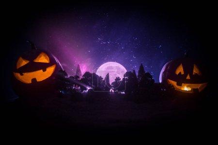 Photo pour Concept d'Halloween avec citrouilles rougeoyantes. Étrange silhouette dans une sombre forêt fantasmagorique dans la nuit, mystique paysage surréalistes lumières avec homme effrayant. Mise au point sélective - image libre de droit