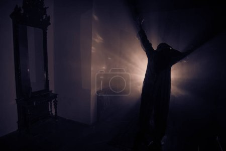 Photo for Horror silhouette of ghost inside dark room with mirror. Scary halloween concept. Silhouette of witch inside haunted house with fog and light on background. Selective focus - Royalty Free Image