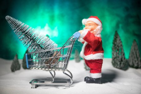 Photo for New year or Christmas holiday shopping concept. Store promotions. Santa Claus carrying trolley cart with gifts on snow - Royalty Free Image