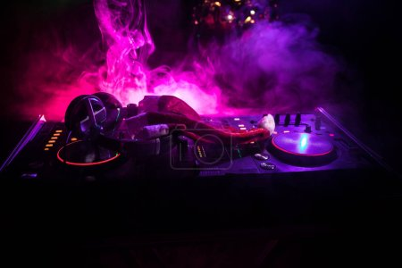 Photo for Dj mixer with headphones on dark nightclub background with Christmas tree New Year Eve. Close up view of New Year elements on a Dj table. Holiday party concept. Empty space - Royalty Free Image