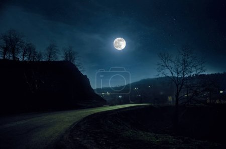 Photo for Mountain Road through the forest on a full moon night. Scenic night landscape of country road at night with large moon - Royalty Free Image