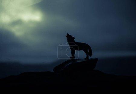 Photo pour Silhouette de loup hurlant sur fond brumeux foncé. Concept d'horreur Halloween. Décoration d'art. Concentration sélective - image libre de droit