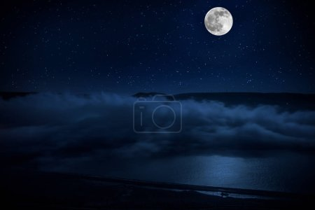 Photo pour Cette élévation spectaculaire de la lune dans un ciel nocturne bleu profond est accentuée par des nuages en surbrillance et une belle réflexion calme du lac . - image libre de droit