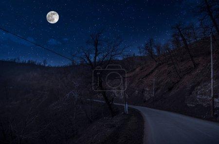 Photo pour Mountain Road à travers la forêt par une nuit de pleine lune. Paysage nocturne pittoresque de la route de campagne la nuit avec grande lune - image libre de droit