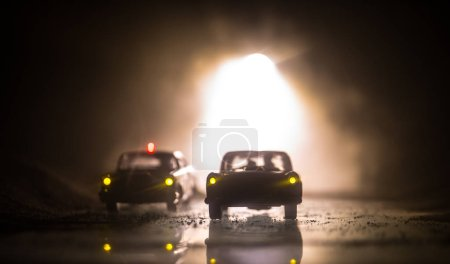 Police car chasing a car at night with fog backgro...