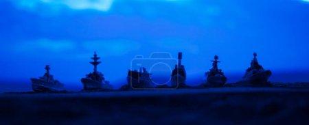 Photo pour Navires de la marine militaire dans une baie au coucher du soleil. Décoration de table d'oeuvre. Concentration sélective - image libre de droit
