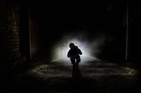 Photo pour Scène d'horreur d'un fantôme effrayant pour enfants, Silhouette d'une poupée effrayante sur fond sombre brumeux avec de la lumière. Horreur concept Halloween - image libre de droit
