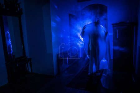 Photo pour Horreur silhouette de fantôme à l'intérieur chambre sombre avec miroir. Concept effrayant d'Halloween. Silhouette de sorcière à l'intérieur de la maison hantée avec brouillard et lumière sur fond. Concentration sélective - image libre de droit