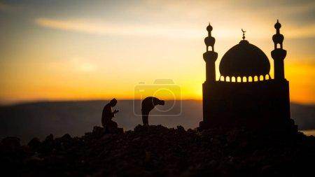Photo pour Concept de religion Islam. Silhouette d'homme priant sur le fond d'une mosquée au coucher du soleil. Carte de vœux festive, invintation pour les fêtes musulmanes - image libre de droit