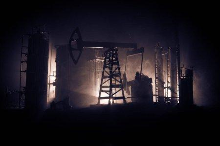 Photo pour Pompe à huile et usine de raffinage de pétrole la nuit avec brouillard et rétroéclairage. Concept énergétique industriel. Concentration sélective. Décoration d'oeuvre . - image libre de droit