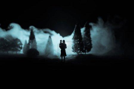 Photo pour Silhouette de femme avec enfant marchant au cimetière la nuit. Horreur concept Halloween. Décoration de table avec lumière et fumée. Concentration sélective - image libre de droit