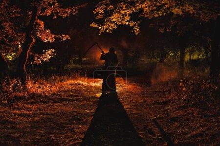 Photo pour Mort avec une faux dans la sombre forêt brumeuse. Fantôme d'horreur femme tenant faucheuse dans la forêt, concept d'Halloween - image libre de droit