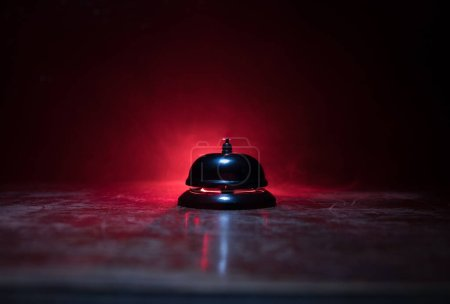 Photo for Calling service bell on wooden table with toned lights on dark background. Hotel reception bell, service bell on the table, selective focus - Royalty Free Image