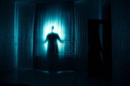 Photo pour Horreur silhouette dans la fenêtre avec rideau à l'intérieur chambre la nuit. Scène d'horreur. Concept d'Halloween. Silhouette floue du fantôme - image libre de droit