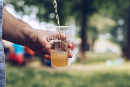 Photo pour Gros plan de verser de la bière dans une tasse en plastique lors d'un pique-nique à l'extérieur - image libre de droit