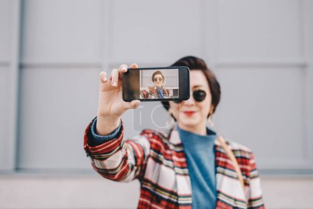 Photo for Close up portrait of pretty and modern young woman taking a selfie with her mobile phone, wearing fancy clothes and posing for friends on social media. Focus on smartphone screen. - Royalty Free Image