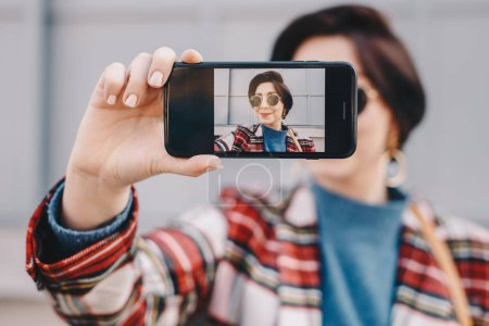 Photo for Close-up portrait of pretty and modern young fashion guru taking a selfie with her mobile phone, wearing fashionable clothes and posing for friends on social media. Focus on smartphone screen. - Royalty Free Image