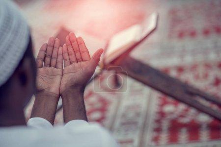 Photo pour Top viewv de l'homme musulman africain faisant la prière traditionnelle à Dieu tout en portant un chapeau traditionnel Dishdasha . - image libre de droit