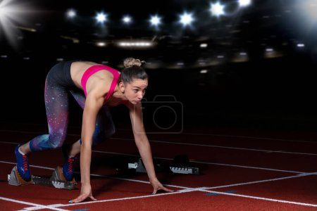 Photo for Woman sprinter leaving starting blocks on the athletic track. exploding start on stadium with reflectors. - Royalty Free Image