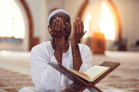 Photo pour Africain musulman faire la prière traditionnelle à Dieu tout en portant Dishdasha . - image libre de droit