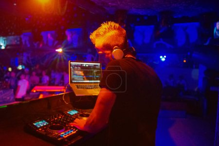 Photo pour Club, disco Dj jouant et mélanger de la musique pour la foule de gens heureux. Vie nocturne, lumières concert, fusées éclairantes - image libre de droit