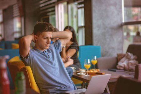 Young skilled male freelancer starting working day early in morning drinking coffee to wake up