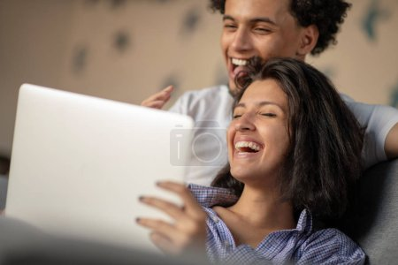 Cheerful happy African American young marriage laughing while watching movie on laptop computer at home interior.