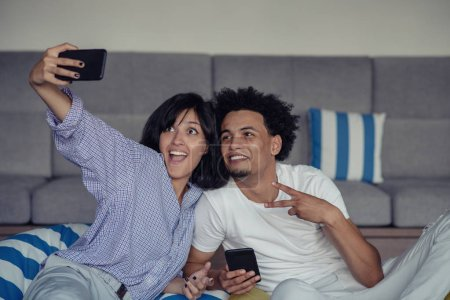 Smiling young couple taking selfies in bed using a smartphone, they are lying down and posing