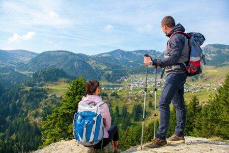 Photo pour Deux randonneurs au belvédère dans les montagnes profitant d'une belle vue sur la vallée avec un lac et un temps chaud ensoleillé en été, des arbres verts autour - image libre de droit