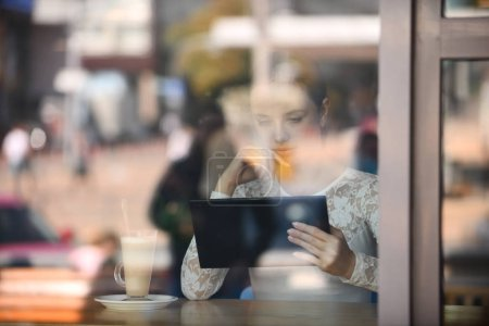 Young woman working, communicating with tablet, dr...