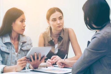 Foto de Mujeres empresarias multiculturales grupo de trabajo discuten en la reunión del grupo en la oficina. Cooperación de la diversidad étnica. - Imagen libre de derechos