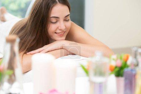 Photo pour Femme détendue couchée sur un lit de spa pour un massage aromathérapie dans un spa de luxe avec un avant-plan flou de soins spa comprenant de l'huile aromatique, une bougie et un gommage aux herbes. Concept de bien-être et guérison . - image libre de droit