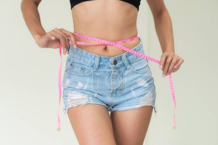Young slim woman measures her waist by measuring t...