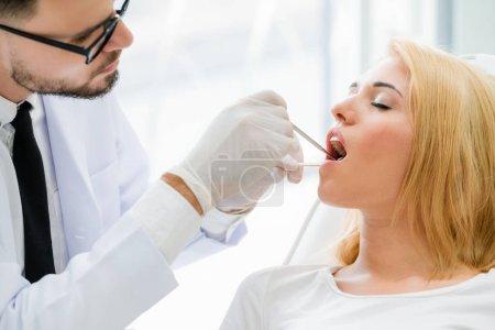 Photo pour Jeune beau dentiste examine les dents de femme heureuse patient assis sur la chaise de dentiste dans une clinique dentaire. Concept de soins dentaire. - image libre de droit