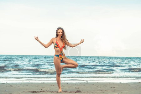 Photo for Young woman practicing yoga pose on the beach in summer. Healthy lifestyle and meditation. - Royalty Free Image